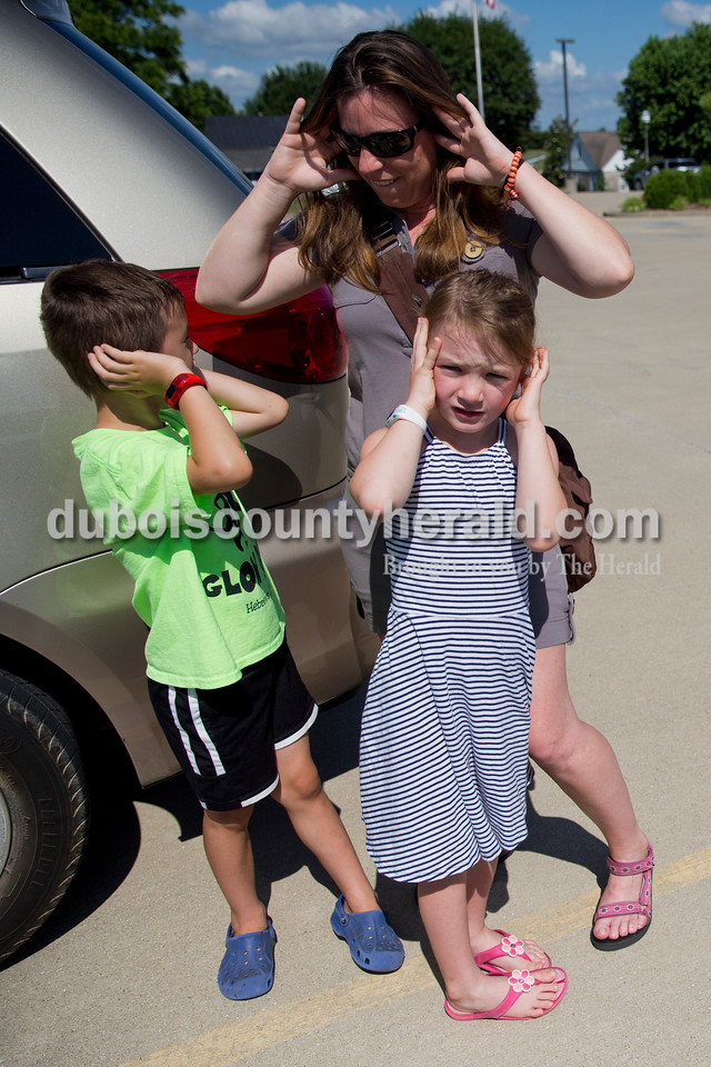 Sarah Ann Jump/The Herald<br /> Emi Steczyk of Ferdinand and her five-year-old twins Casey, left, and Dylan covered their ears as police officers prepared to sound the sirens on the patrol car after story time with Ferdinand Police officers at the Ferdinand Public Library on Tuesday morning.