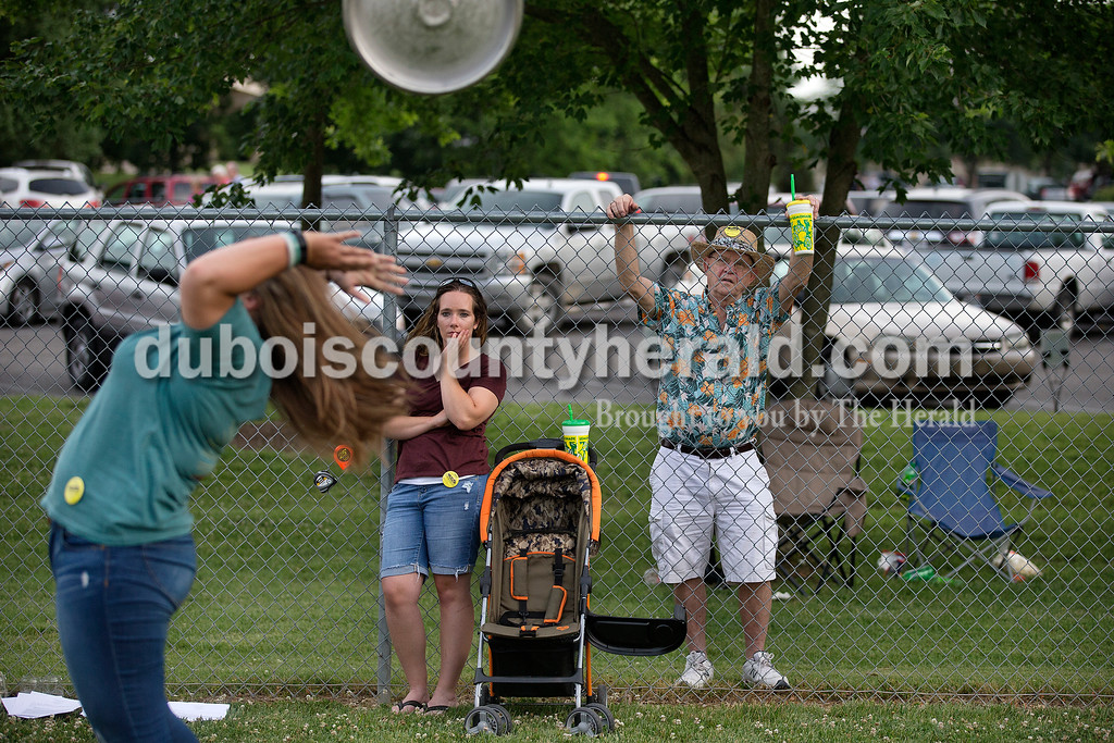 """Brittney Lohmiller /The Herald <br /> Rachel Chattin of Washington tossed a beer keg behind her back while Lori Merkel and Raymond Buechlein, both of Ferdinand, watched during Heimatfest at 18th Street Park Friday evening. """"I just came to watch then got bullied into it,"""" Chattin said."""