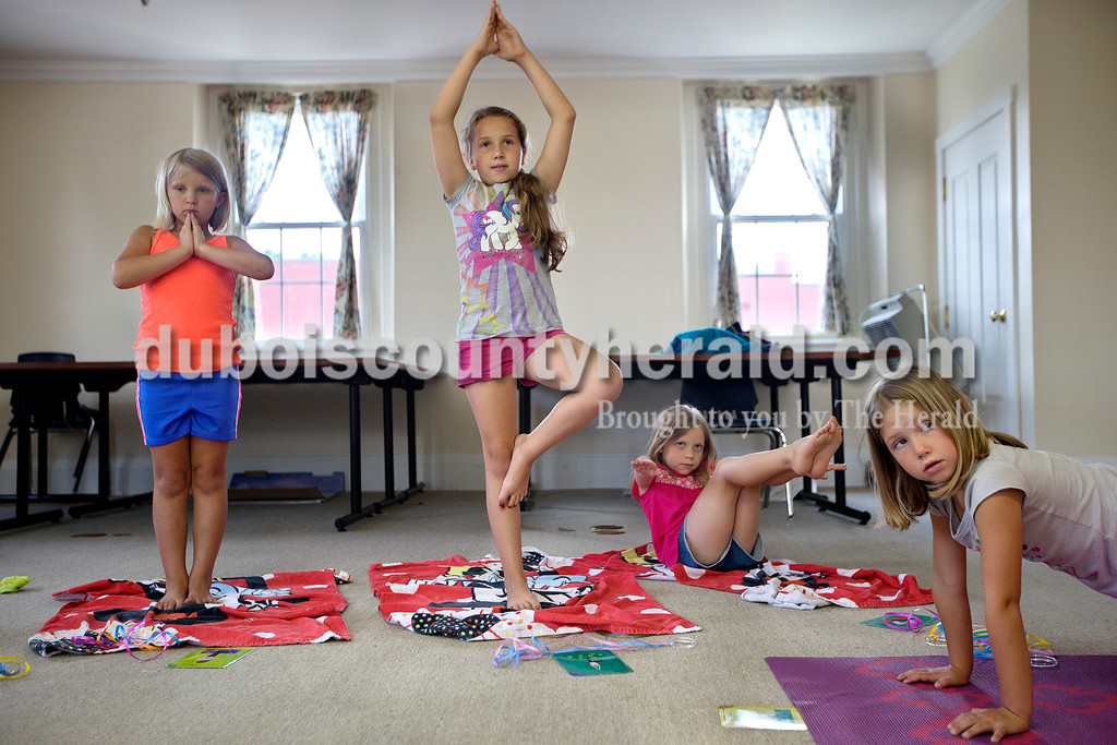 """Brittney Lohmiller/The Herald <br /> From left: Jacey Booker, 7, Izabelle Hollingsworth, 9, Ryla Czerwinski, 8, and Haddie Hollingsworth, 6, all of Jasper, practiced different yoga poses at the Jasper Public Library Annex Wednesday afternoon. Amanda Gamble, a registered yoga instructor with Fire Horse Yoga Studio, taught 13 children different poses as well as breathing exercises during the hour long class. """"I though this would be great to use with kids in the school system,"""" Gamble, a school psychologist, said. """"Teaching mindfulness and breathing exercises helps with stress."""""""
