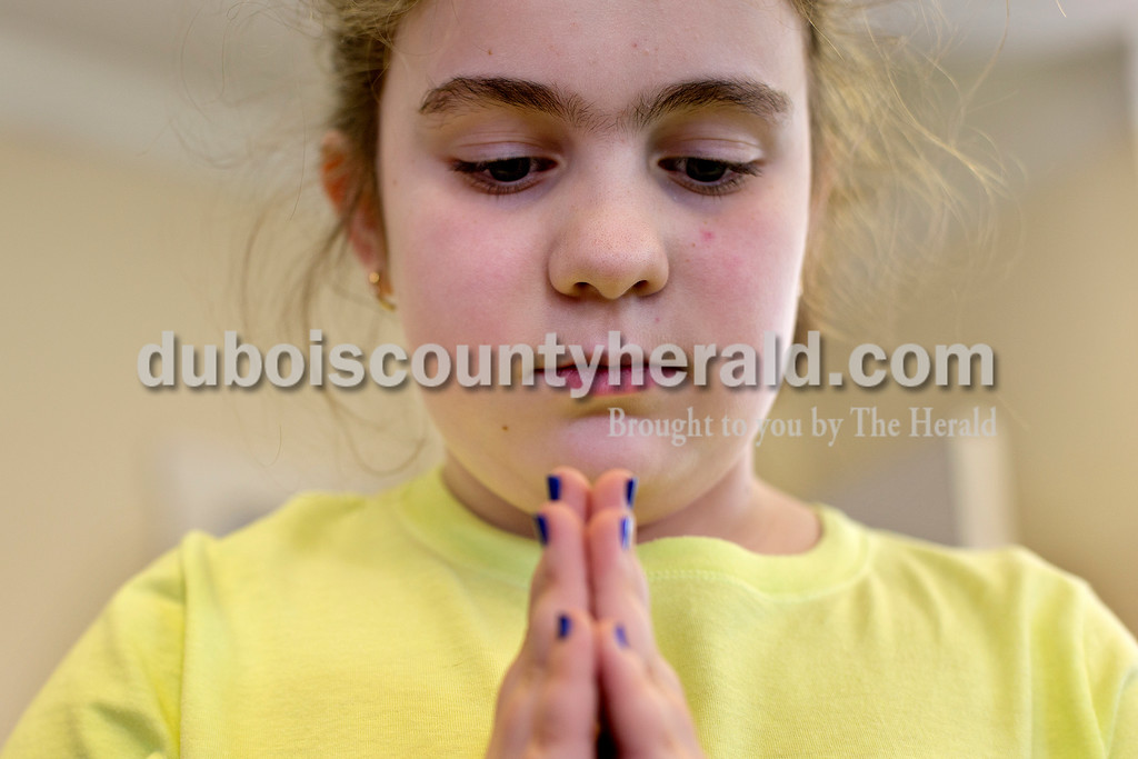 Brittney Lohmiller/The Herald <br /> Kaitlyn Meyer of Dubois, 8, stared at a space on the floor while she practiced the tree pose during a yoga class for kids at the Jasper Public Library Annex Wednesday afternoon.