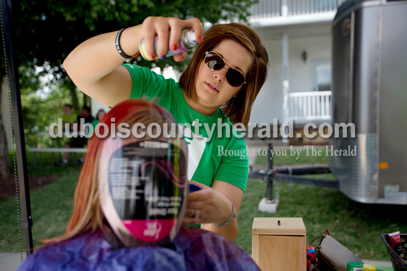Brittney Lohmiller/The Herald <br /> April Thewess of Celestine sprayed colored hair spray onto Riley Esarey of Santa Claus, 10, Saturday afternoon during the 7th Celestine Streetfest.