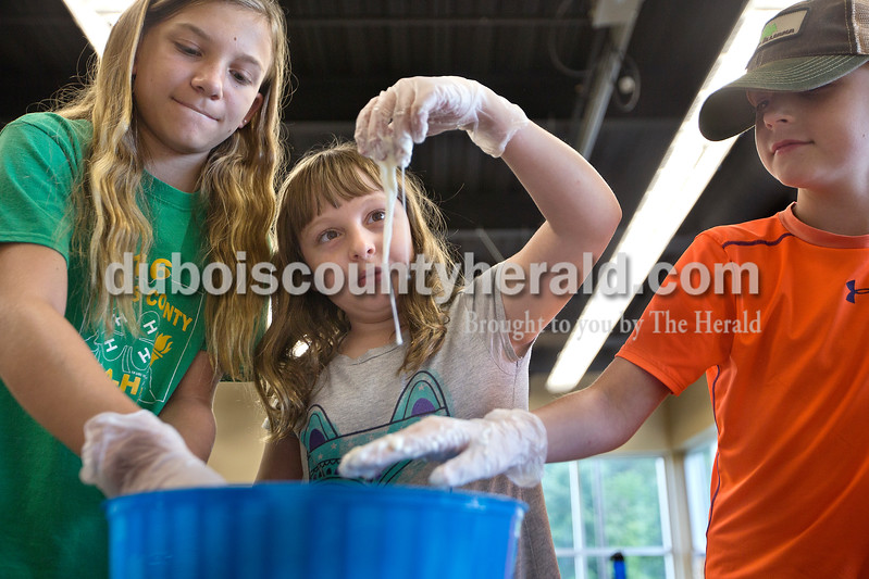 "Brittney Lohmiller /The Herald <br /> Ashlin Mehringer of Haysville, 11, left, Adonica Meyer, 9, and Mitchel Huebner, 9, both of Jasper, played with oobleck as part of Vincennes University Jasper Campus' Kids' College summer programming Ooey, Goey Creations and More Monday afternoon. ""It's like a solid and a liquid,"" Meyer said as she watched the oobleck slide down her fingers. Oobleck is non-Newtonian fluid made of water and cornstarch."