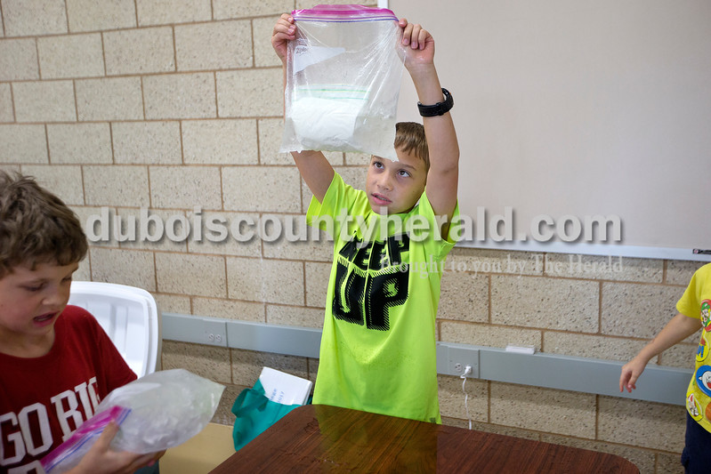 Brittney Lohmiller /The Herald <br /> Paxton Mehringer of Haysville, 10, checked to see if his bag containing milk, sugar, vanilla extract and cream was leaking into the ice during Vincennes University Jasper Campus' Kids' College summer programming Ooey, Goey Creations and More Monday afternoon. Seventeen children ranging in ages from 8 to 11 participated in hands on Science Technology Engineering and Mathematics (STEM) activities throughout the afternoon.