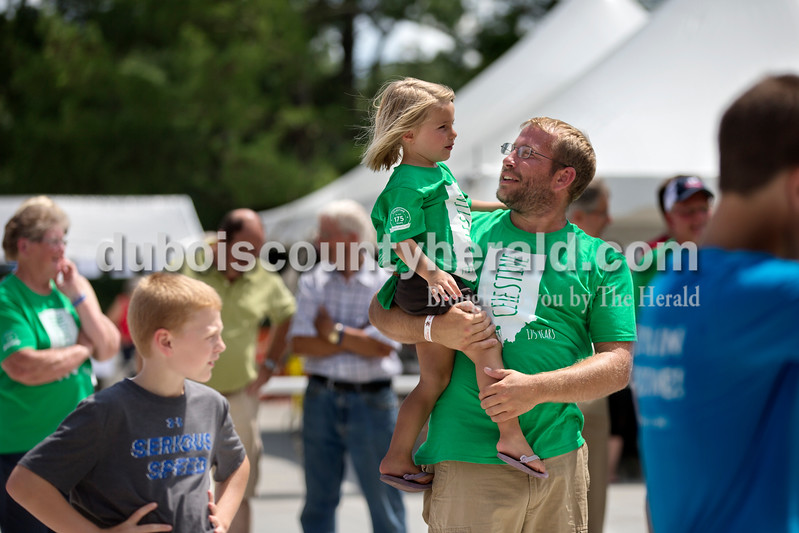 Brittney Lohmiller/The Herald <br /> Todd Goepfrich held his daughter Kaelyn Goepfrich, 3 , both of Celestine as they watched people participate in dunk booth Saturday afternoon during the 7th annual Celestine Streetfest. Members of the fire department, St. Celestine Catholic Church and school participated in the sitting in the dunking booth for 30 minutes while attendees got three chances to try and dunk them.
