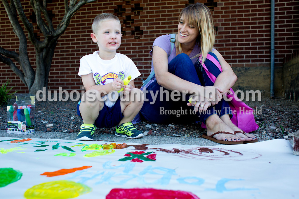 Tegan Johnston/The Herald<br /> Amanda Smith of Jasper painted with her son, Henry, 3, during Wednesday's Outside Art Day at the Jasper Public Library. Families spent the morning working on a variety of crafts, which included coloring visors, making animal masks, decorating sticker sheets, painting and more.
