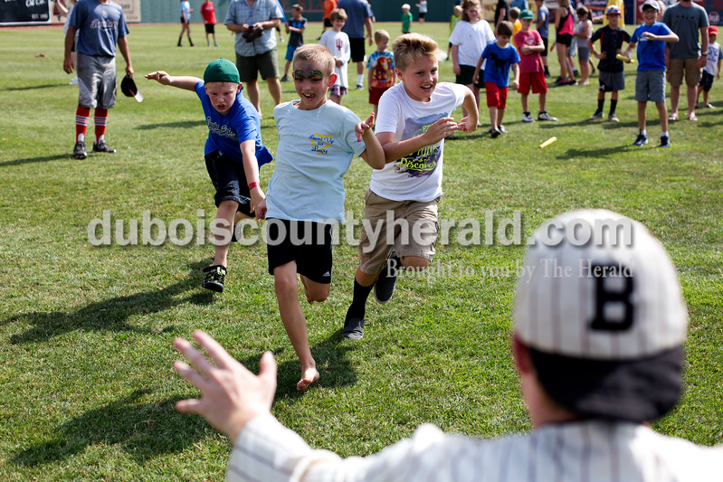 "Tegan Johnston/The Herald<br /> Caiden Beck of Ferdinand, 8, from left, Gavin Jones of Duff, 9, and Dane Butcher of Lynnville, 9, raced to the mascot ""Casey"" while playing games during Saturday's 25th anniversary celebration of the film ""A League of Their Own"" at League Stadium in Huntingburg."