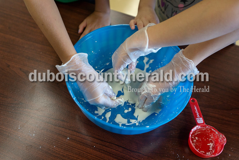 "Brittney Lohmiller /The Herald <br /> Ashlin Mehringer of Haysville, 11, left, Adonica Meyer, 9, and Mitchel Huebner, 9, both of Jasper, mixed water and cornstarch to make oobleck as part of Vincennes University Jasper Campus' Kids' College summer programming Ooey, Goey Creations and More Monday afternoon. ""It's like a solid and a liquid,"" Meyer said as she watched the oobleck slide down her fingers. Oobleck is non-Newtonian fluid made of water and cornstarch."