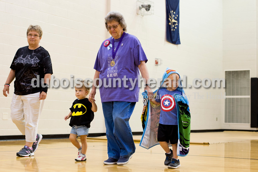 "Tegan Johnston/The Herald<br /> Cancer survivor Pat Gadlage of Jasper walked laps around the gym while holding hands with her great-grandchildren Madison Kieser of Jasper, 2, and her brother, Brandon, 3, during the 2017 Dubois County Relay for Life on Saturday at Jasper Middle School in Jasper. The theme for this year's ceremony was ""Not all superheroes wear capes."" Different events and activities were planned throughout the day for fighters, survivors and families supporting the cause."
