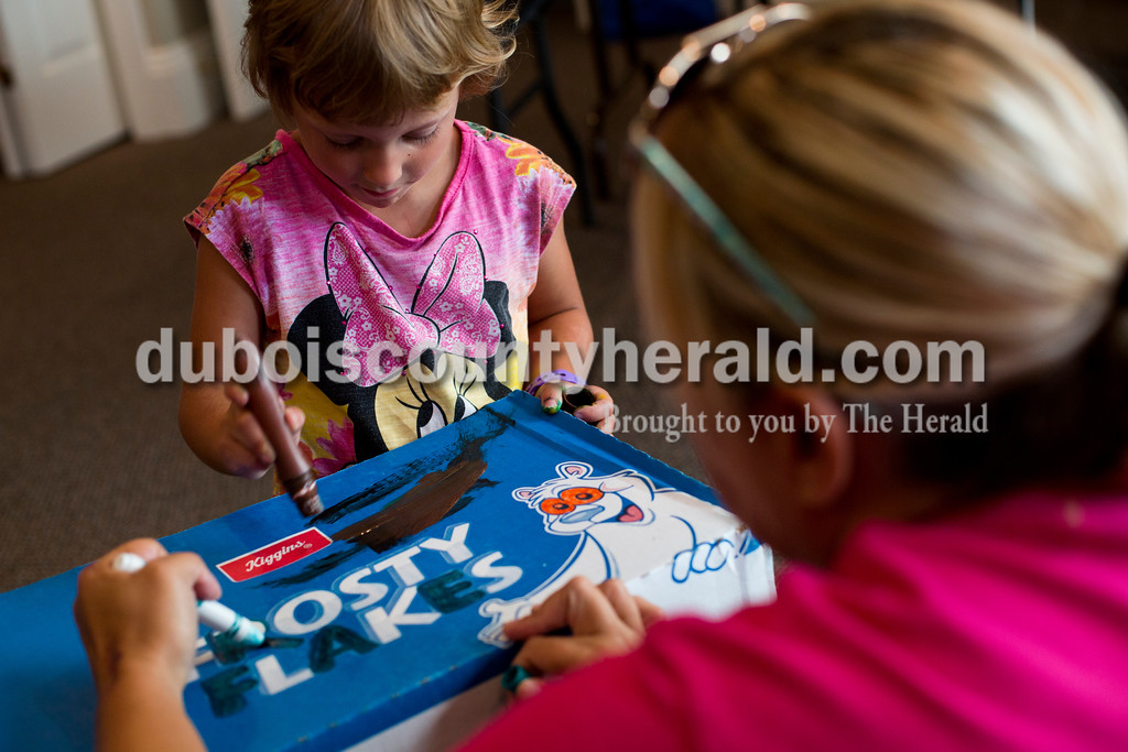 Tegan Johnston/The Herald<br /> Echo Hankison of Loogootee, 4,  painted her box car with Tina Himsel of Washington during Thursday's Cardboard Car Project at the Jasper Public Library Annex. The library provided paint, stickers, plastic plates, cups and more for children to decorate their boxes.