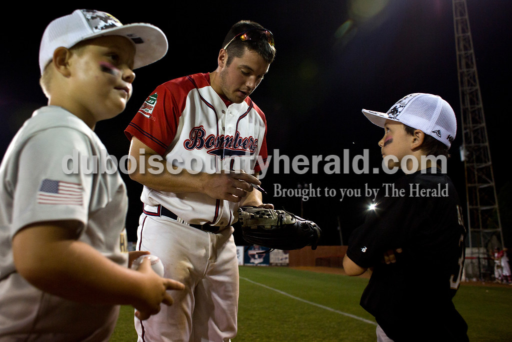 Tegan Johnston/The Herald<br /> Dubois County Bombers' Brandon Smith signed a glove for Ethan Archer of French Lick, 8, after Tuesday night's game at League Stadium in Huntingburg. The Bombers defeated Paducah 8-2.