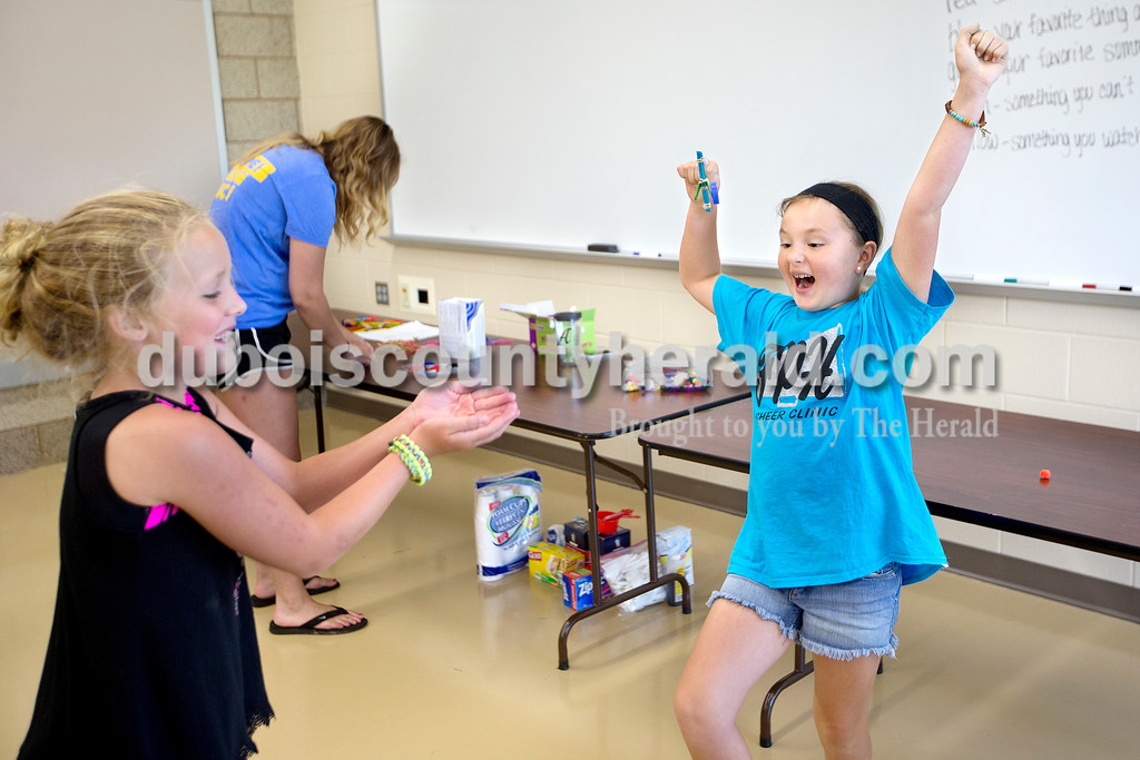 "Brittney Lohmiller /The Herald <br /> Leigha Nord of St. Anthony, 8, right, celebrated as Chloe Tooley of Huntingburg, 10, caught a puffed ball Nord launched from her catapult during Vincennes University Jasper Campus' Kids' College summer programming Ooey, Goey Creations and More Monday afternoon. Program instructors Katelynn Schnell and Abby Rogier showed students how to make oobleck, ice cream in a bag and giant water beads. ""We did a STEM class last year and this year we split the class into two, to give them a more hands on experience,"" Schnell said."