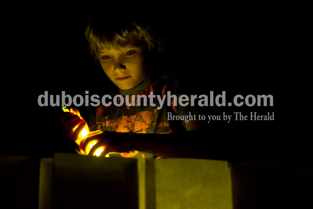 "Tegan Johnston/The Herald<br /> Wylon Schoppenhorst of Velpen, 9, lit a glow stick during the luminaria ceremony at the 2017 Dubois County Relay for Life on Saturday at Jasper Middle School in Jasper. The theme for this year's ceremony was ""Not all superheroes wear capes."" Different events and activities were planned throughout the day for fighters, survivors and families supporting the cause."