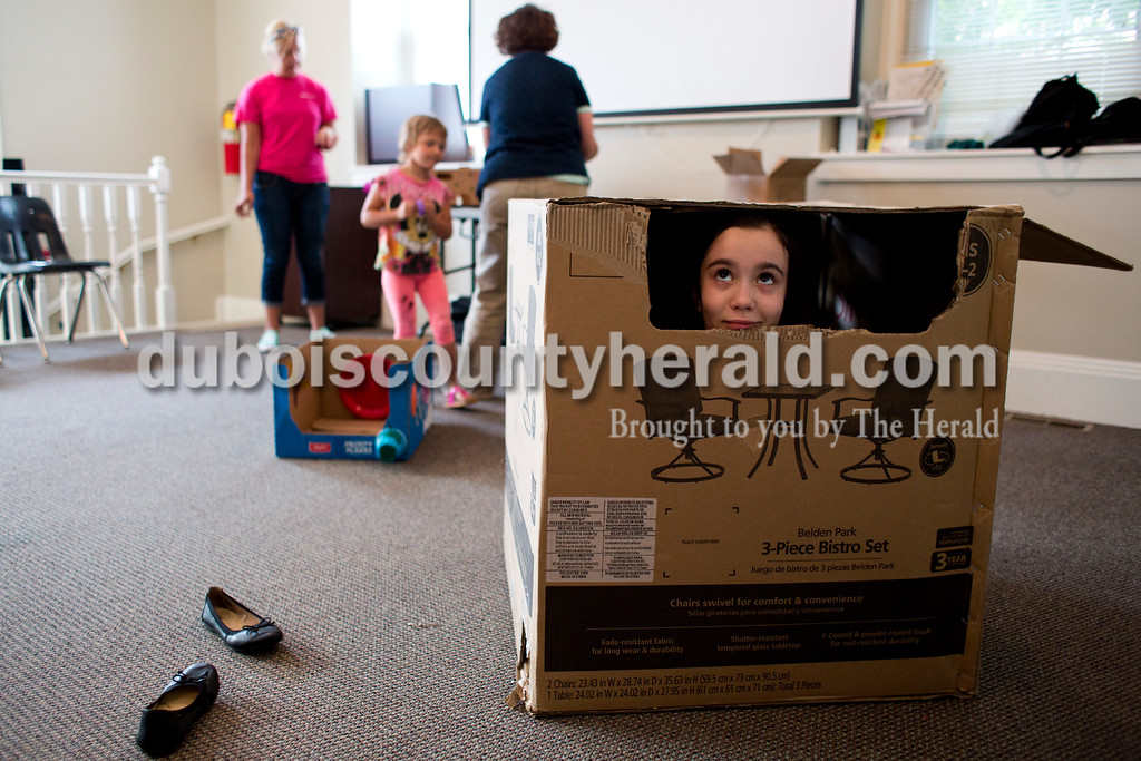 Tegan Johnston/The Herald<br /> Madeline Zipp-Nathan of Jasper, 9, peaked out of the box she was decorating during Thursday's Cardboard Car Project at the Jasper Public Library Annex. The library provided paint, stickers, plastic plates, cups and more for children to decorate their boxes.