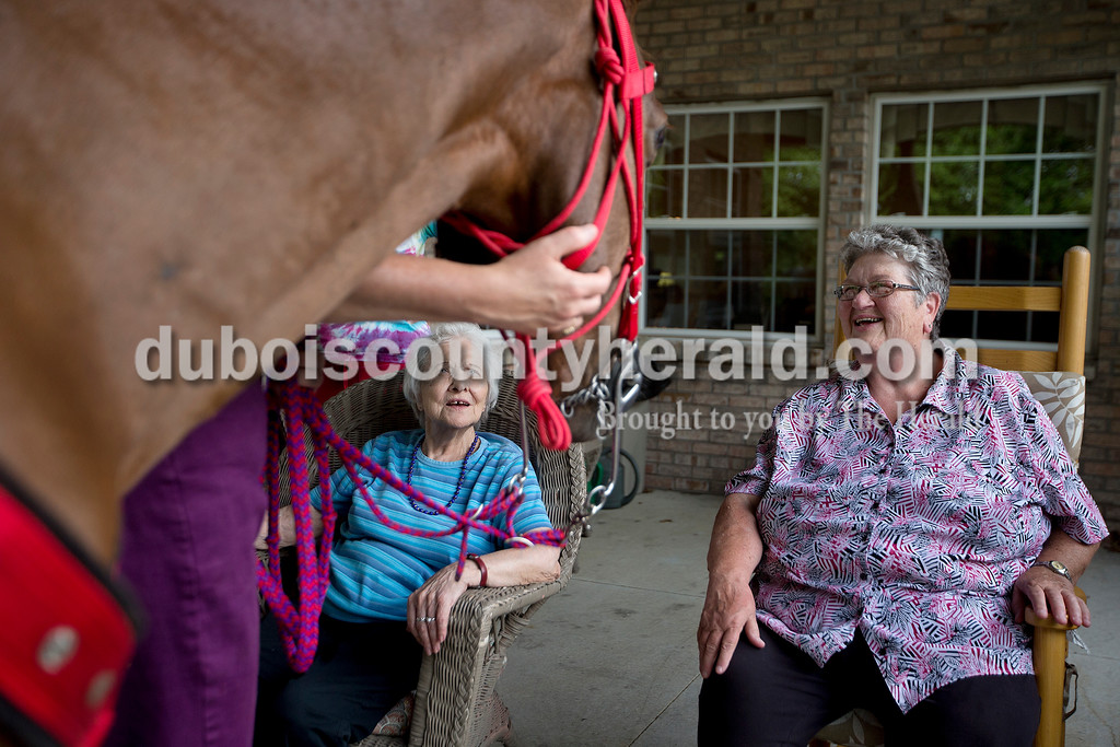Brittney Lohmiller /The Herald <br /> Red Hats Purple Chaps of Indiana member Janet Welp, left, held her horse, Merry, steady while she chatted with Brookside Senior Living Community resident Mary Grose, left, and Nancy Lottes of Jasper Wednesday evening.