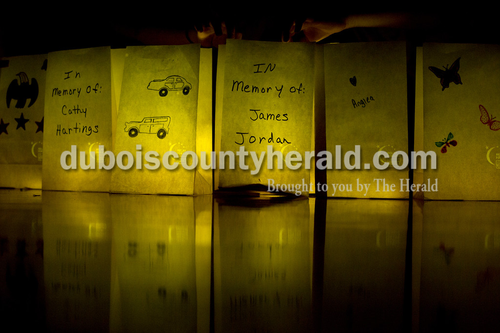 "Tegan Johnston/The Herald<br /> Commemorative bags were decorated and lit with glow sticks during the luminaria ceremony at the 2017 Dubois County Relay for Life on Saturday at Jasper Middle School in Jasper. The theme for this year's ceremony was ""Not all superheroes wear capes."" Different events and activities were planned throughout the day for fighters, survivors and families supporting the cause."