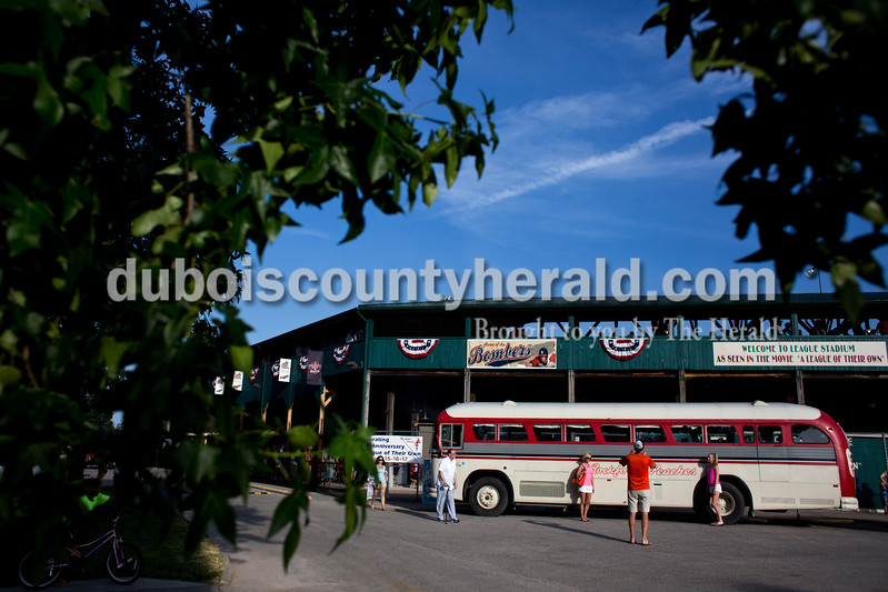 "Tegan Johnston/The Herald<br /> Mike Browning of St. Louis, Mo., took a photo of his wife, Nicole, left, and daughter, Carly, 15, as they posed in front of the Rockford Peaches' bus during Saturday's 25th anniversary celebration of the film ""A League of Their Own"" at League Stadium in Huntingburg."