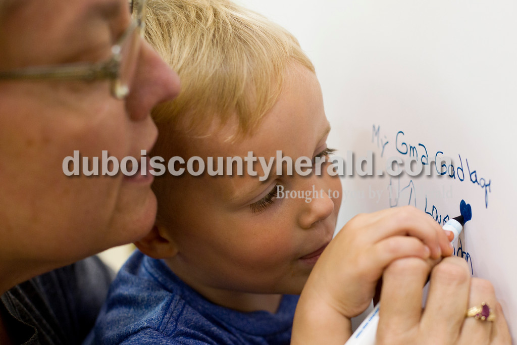 "Tegan Johnston/The Herald<br /> Angie Kieser of Jasper held her grandson Brandon Kieser of Jasper, 3, while helping him write ""My Superhero is...my Gma Gadlage"" on the Superhero wall during the 2017 Dubois County Relay for Life on Saturday at Jasper Middle School in Jasper. Brandon's great-grandmother, Pat Gadlage, is a cancer survivor. The theme for this year's ceremony was ""Not all superheroes wear capes."" Different events and activities were planned throughout the day for fighters, survivors and families supporting the cause."