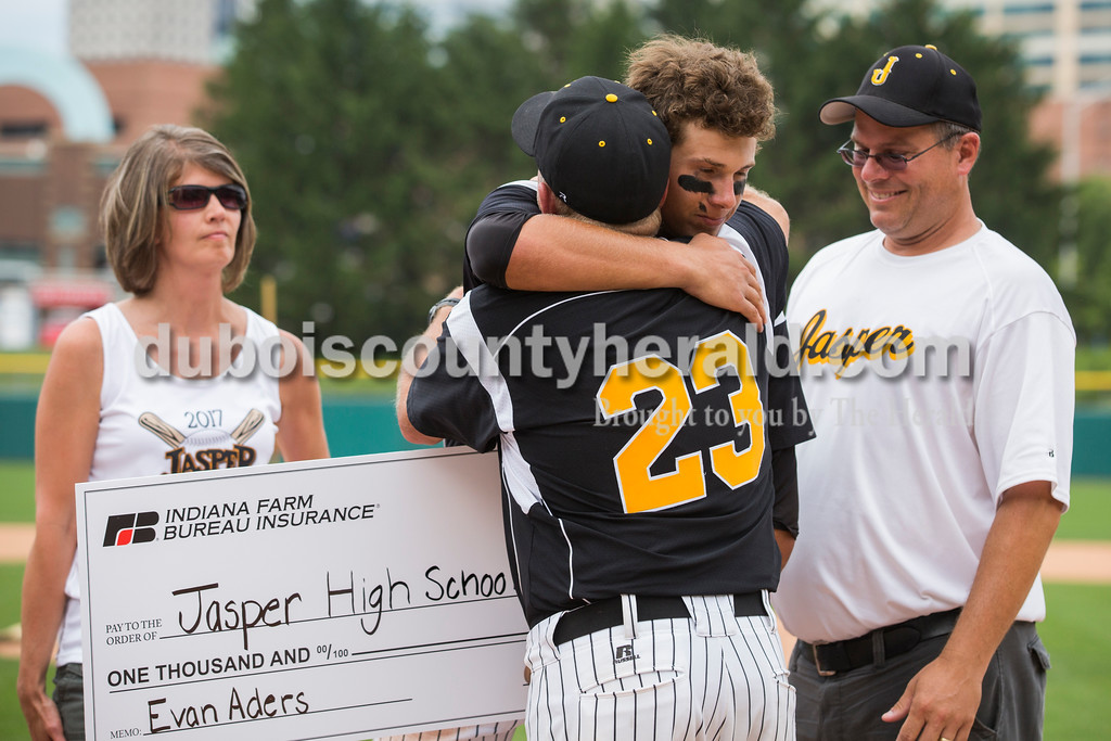 Jasper's Evan Aders, flanked by his parents Pam and Doug, hugged coach Terry Gobert after being presented with the L.V. Phillips Mental Attitude Award during Saturday's Class 3A baseball state championship game at Victory Field in Indianapolis. South Bend St. Joseph defeated Jasper 4-0. Sarah Ann Jump/The Herald