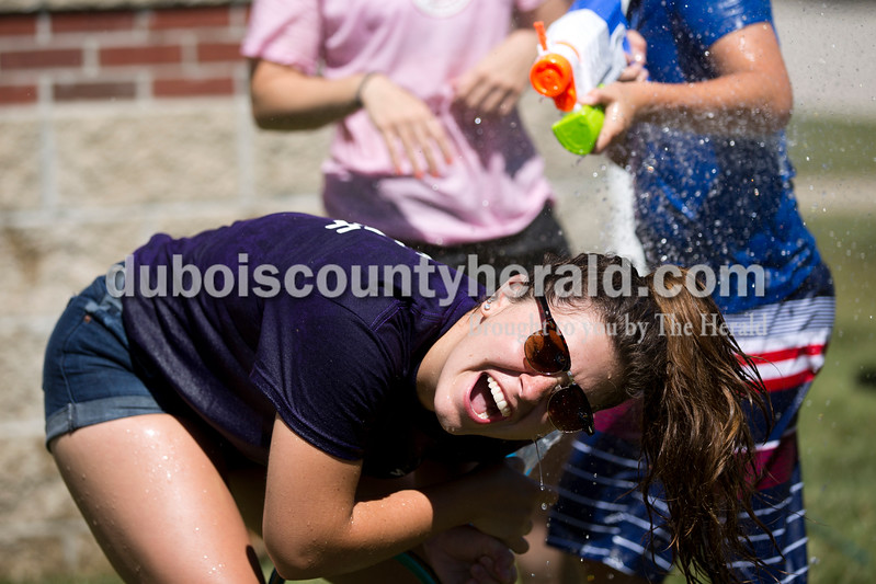 Sarah Ann Jump/The Herald<br /> Rockford Peach Shelby Klem of Ferdinand tried to take cover as Owen Schuetter of Ferdinand, 10, sprayed her during Water Wars with the Dubois County Bombers at the Ferdinand Public Library on Tuesday.
