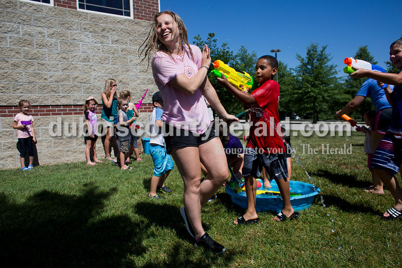 "Sarah Ann Jump/The Herald<br /> Rockford Peach Kayla Hoffman of Ferdinand was sprayed by Hayden Akpan of Ferdinand, 10, during Water Wars with the Dubois County Bombers at the Ferdinand Public Library on Tuesday. <br /> ""Since everyone is from different places, it's good to get to know the people of Dubois County,"" said Bombers player Zack Gray. <br /> ""We enjoy being positive role models for the youth. This is a really fun way to spend my summer,"" said Rockford Peach Shelby Klem."