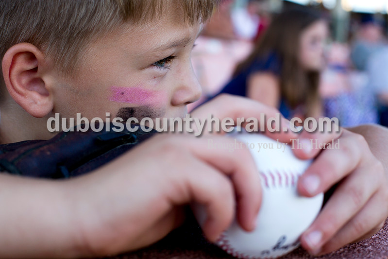 Tegan Johnston/The Herald<br /> Elijah Dickey of French Lick, 8, held onto his signed baseball as he watched Tuesday night's game at League Stadium in Huntingburg. The Bombers defeated Paducah 8-2.