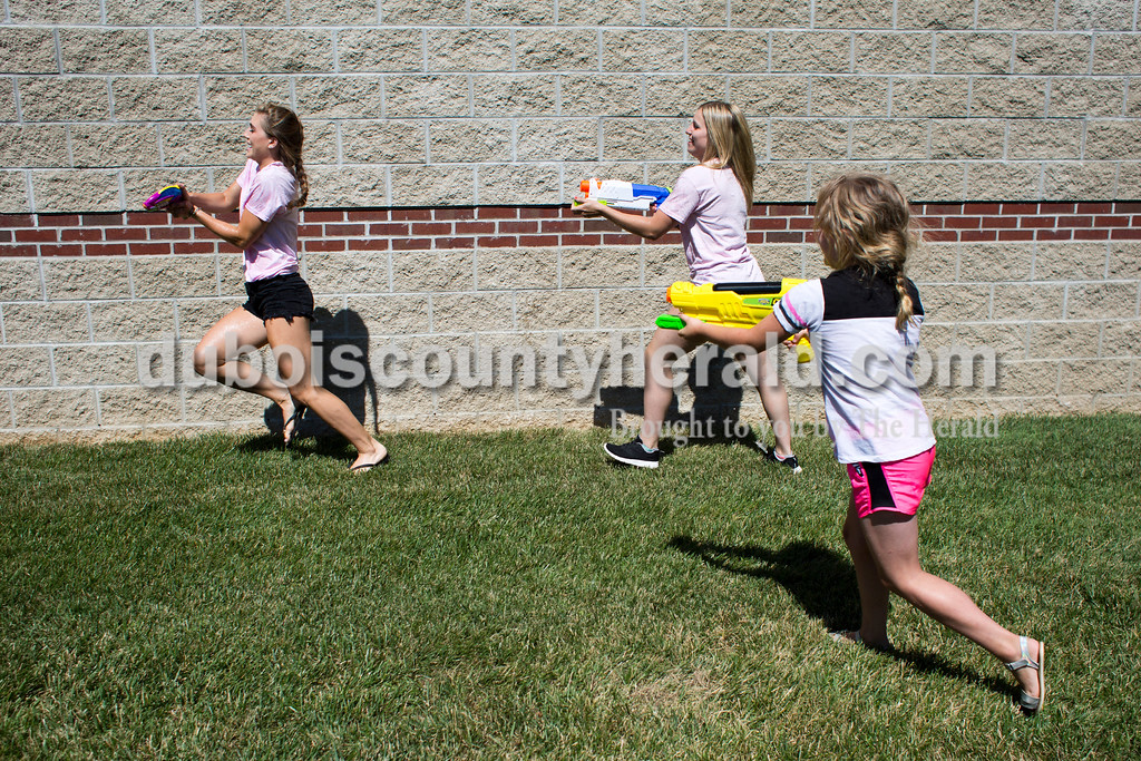 Sarah Ann Jump/The Herald<br /> Rockford Peach Lauren Meyer of Ferdinand, left, was chased by Peach Kayla Hoffman of Ferdinand and Brooklyn Fleig of Ferdinand, 6, during Water Wars with the Dubois County Bombers at the Ferdinand Public Library on Tuesday.
