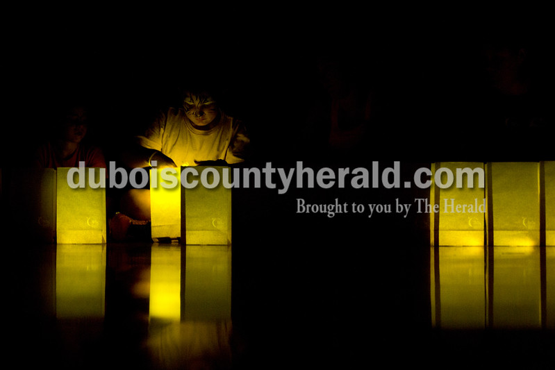 "Tegan Johnston/The Herald<br /> Corvin Hoffman of Mentor, 9, placed a glow stick in one of the commemorative bags during the luminaria ceremony at the 2017 Dubois County Relay for Life on Saturday at Jasper Middle School in Jasper. The theme for this year's ceremony was ""Not all superheroes wear capes."" Different events and activities were planned throughout the day for fighters, survivors and families supporting the cause."
