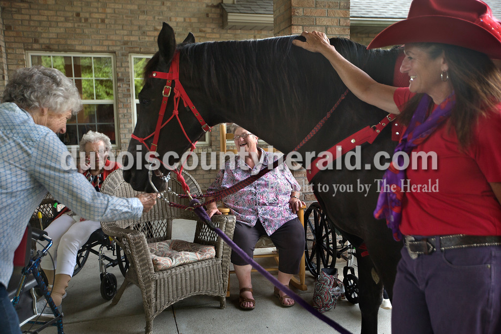 "Brittney Lohmiller /The Herald <br /> Brookside Senior Living Community residents Bernida Jochim tickled the muzzle of Red Hats Purple Chaps of Indiana member Anne Mehringer's horse, Skipper, while resident Esther Giesler and Nancy Lottes of Jasper laughed Wednesday evening. ""Are you going to give me a kiss?"" Jochim asked Skipper. ""I never had a pretty horse like this. We used them on the farm to plow but on Sunday afternoons we'd wash and brush them. They loved it."""
