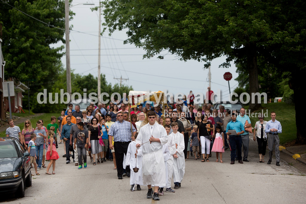 Tegan Johnston/The Herald<br /> Garrett Altmeyer of Huntingburg, held incense while leading Father Ryan Hilderbrand with the sacrament of monstrance and members of St. Mary Catholic Church through the parish neighborhood during Corpus Christi Procession on Sunday. The procession took place directly after the 10 a.m. bilingual mass.