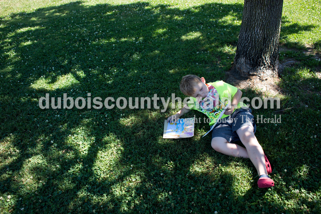 Tegan Johnston/The Herald<br /> Waylon Barker of Jasper, 6, lounged under a tree while he decided what stickers to use to decorate his sticker sheet during Wednesday's Outside Art Day at the Jasper Public Library. Families spent the morning working on a variety of crafts, which included coloring visors, making animal masks, decorating sticker sheets, painting and more.