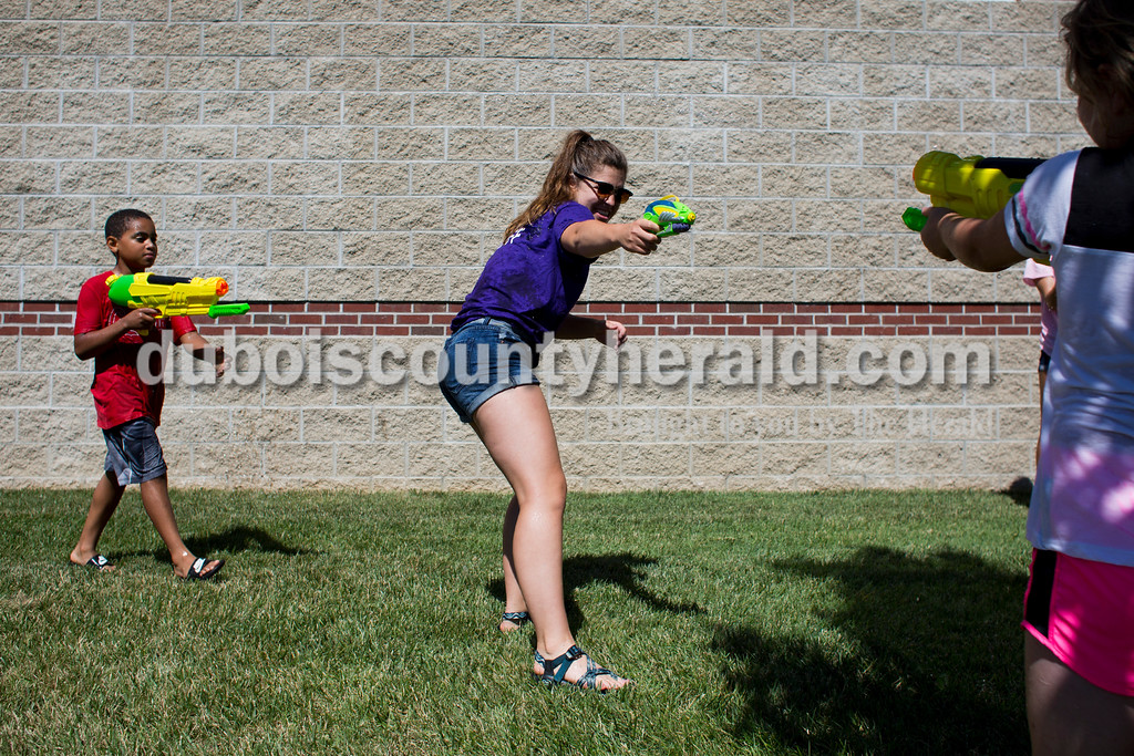 Sarah Ann Jump/The Herald<br /> Rockford Peach Shelby Klem of Ferdinand, center, squirted Brooklyn Fleig of Ferdinand, 10, right, as Hayden Akpan of Ferdinand, 10, left, came from behind during Water Wars with the Dubois County Bombers at the Ferdinand Public Library on Tuesday.