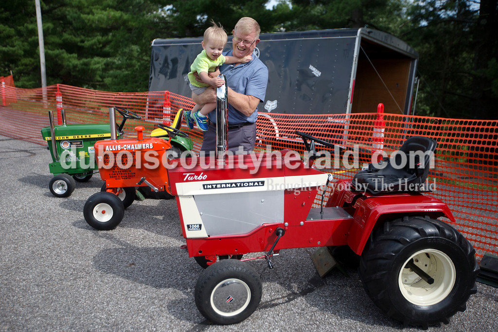 "Brittney Lohmiller/The Herald <br /> Bill Stetter of Dubois held up his grandson Owen Stetter of Schnellville, 2, so he could get a better look at the tractor Saturday afternoon during the 7th annual Celestine Streetfest. ""He likes tractors; he gets to ride one at home"" Stetter said."