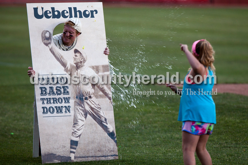 "Tegan Johnston/The Herald<br /> Keyona Sharp of French Lick, 8, threw a water balloon at Kru Allen who was dressed as the mascot ""Casey"" during Tuesday night's game at League Stadium in Huntingburg. The Bombers defeated Paducah 8-2."