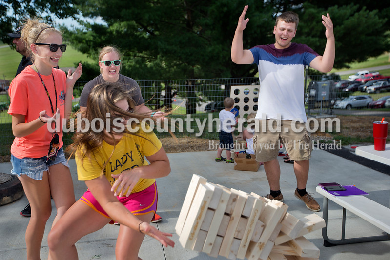 Brittney Lohmiller/The Herald <br /> Taylin Friedman, 18, turned to try and catch the collapsing Jenga game as Claire Schnell, 16, Taryn Friedman and Reece Helming,17, all of Celestine, cried out Saturday afternoon during the 7th annual Celestine Streetfest. Along with booth for games and food a large version of Jenga and Connect 4 were made for attendees to use.