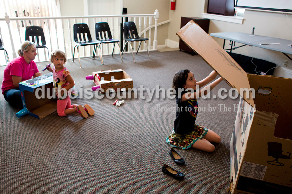 Tegan Johnston/The Herald<br /> Echo Hankison of Loogootee, 4,  and Tina Himsel of Washington, left, watched Madeline Zipp-Nathan of Jasper, 9, decorate her box during Thursday's Cardboard Car Project at the Jasper Public Library Annex. The library provided paint, stickers, plastic plates, cups and more for children to decorate their boxes.