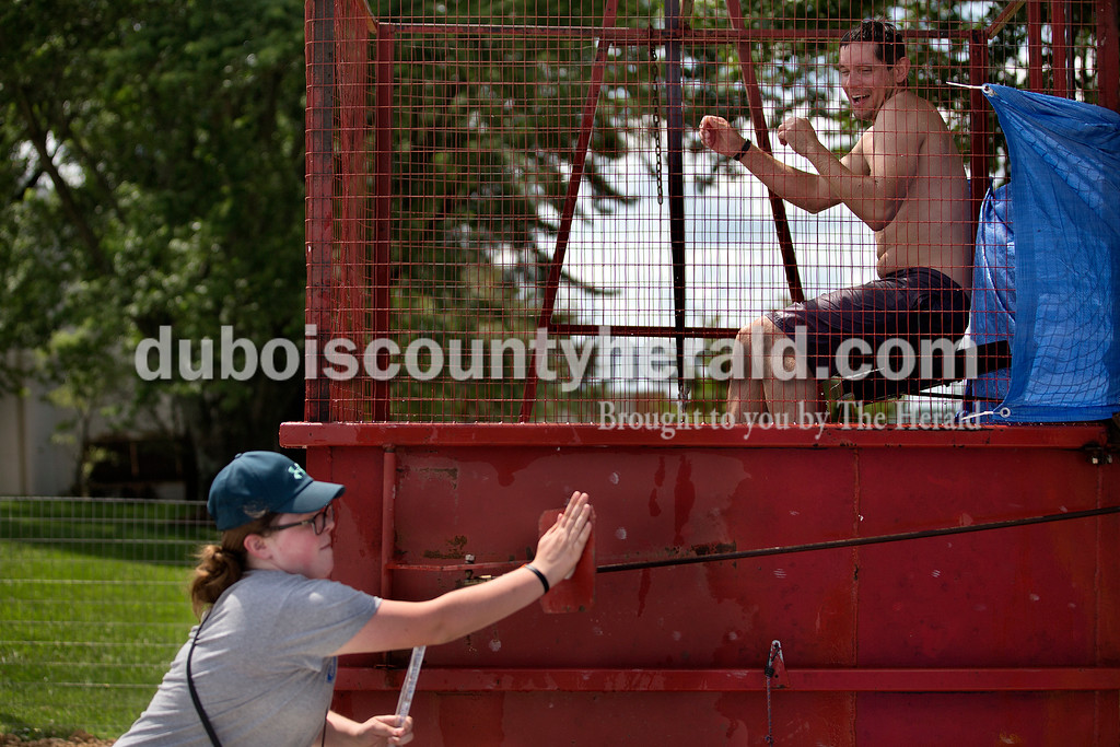 Brittney Lohmiller/The Herald <br /> Madelyn Merkel of Celestine, 11, pressed the target to dunk Celestine Volunteer Fire Department Chief Ryan Wineinger into a container of water Saturday afternoon during the 7th annual Celestine Streetfest. Members of the fire department, St. Celestine Catholic Church and school participated in the sitting in the dunking booth for 30 minutes while attendees got three chances to try and dunk them.