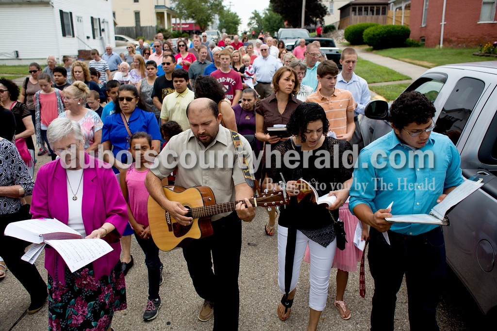 Tegan Johnston/The Herald<br /> Jose Dubon of Huntingburg, center, played his guitar as he led members of St. Mary Catholic Church in song while following Father Ryan Hilderbrand through the the parish neighborhood as he carried the sacrament of monstrance during the Corpus Christi Procession through Huntingburg on Sunday. The procession took place directly after the 10 a.m. bilingual mass.