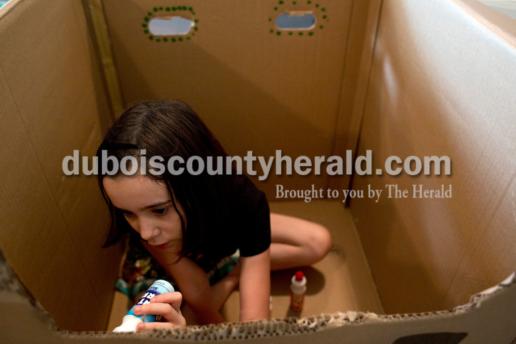 Tegan Johnston/The Herald<br /> Madeline Zipp-Nathan of Jasper, 9, painted her name on the inside of her box during Thursday's Cardboard Car Project at the Jasper Public Library Annex. The library provided paint, stickers, plastic plates, cups and more for children to decorate their boxes.