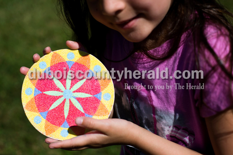 Tegan Johnston/The Herald<br /> Raylee Bastin of Jasper, 5, showed off her craft she made with glitter during Wednesday's Outside Art Day at the Jasper Public Library. Families spent the morning working on a variety of crafts, which included coloring visors, making animal masks, decorating sticker sheets, painting and more.