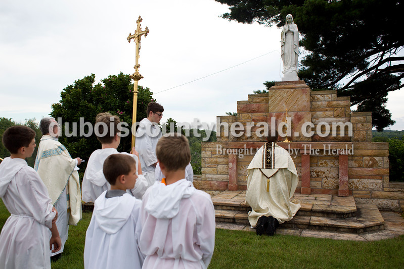 Tegan Johnston/The Herald<br /> Father Ryan Hilderbrand knelt before an alter in the cemetery behind St. Mary Catholic Church during the Corpus Christi Procession through Huntingburg on Sunday. Members of St. Mary Catholic Church in Huntingburg sang and chanted as they followed Father Ryan Hilderbrand through the the parish neighborhood while he carried the sacrament of monstrance. The procession took place directly after the 10 a.m. bilingual mass.