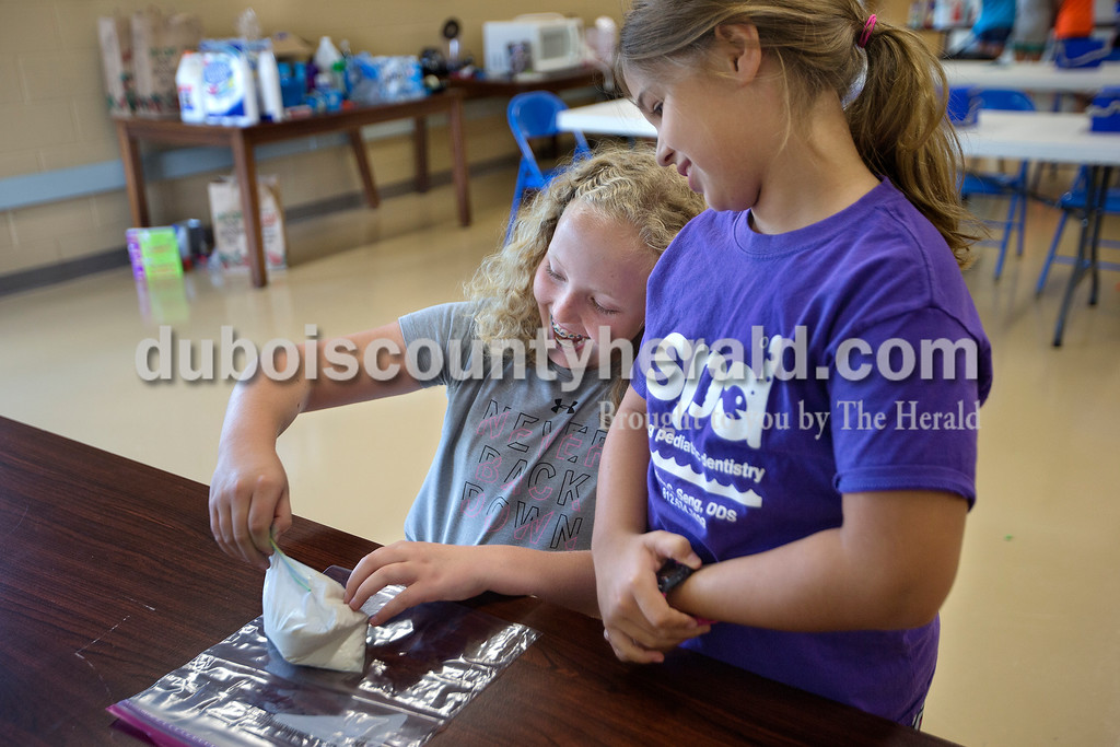 Brittney Lohmiller /The Herald <br /> Caroline Buechlein, 11, left, moved milk, sugar, vanilla extract and cream around in a bag as her sister Anna Buechlein, 8, both of Ireland, watched during Vincennes University Jasper Campus' Kids' College summer programming Ooey, Goey Creations and More Monday afternoon. After shaking the bag inside a second bag of ice and salt the pair created ice cream. Seventeen children ranging in ages from 8 to 11 participated in hands on Science Technology Engineering and Mathematics (STEM) activities throughout the afternoon.