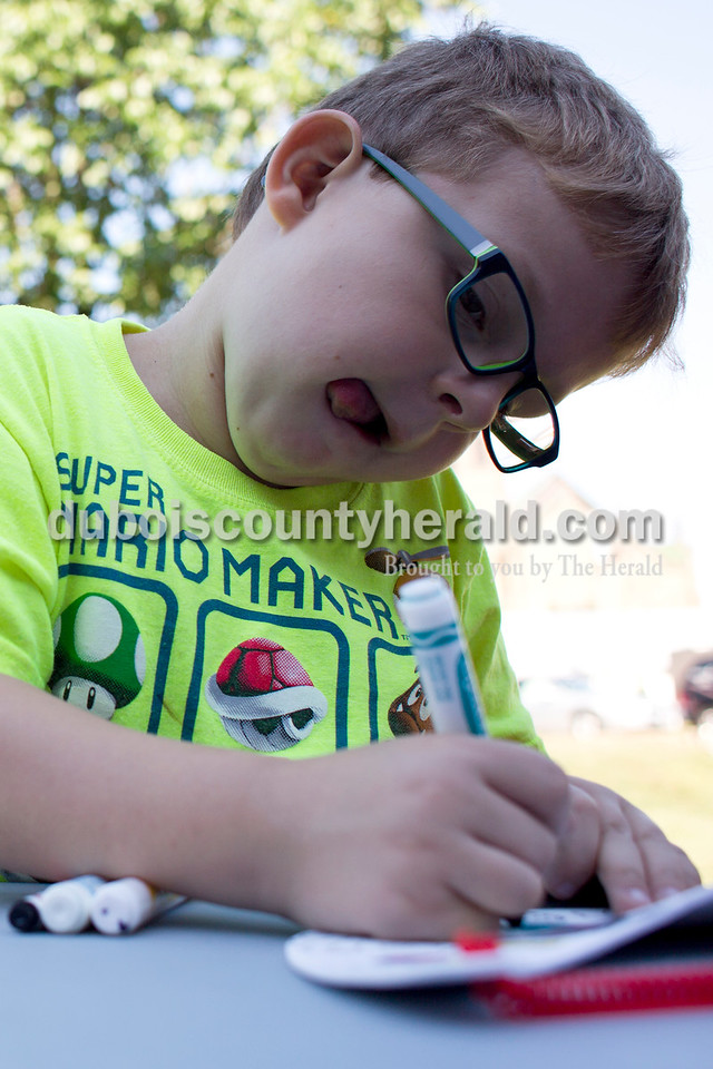Tegan Johnston/The Herald<br /> Waylon Barker of Jasper, 6, focused while coloring his visor during Wednesday's Outside Art Day at the Jasper Public Library. Families spent the morning working on a variety of crafts, which included coloring visors, making animal masks, decorating sticker sheets, painting and more.