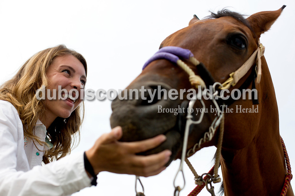 "Tegan Johnston/The Herald<br /> Kennedy Neukam of Dubois, 19, played with her horse ""Red"" before completing in her first rodeo during the Lone Star Rodeo on Saturday at the Dubois County 4-H Fairgrounds in Bretzville."