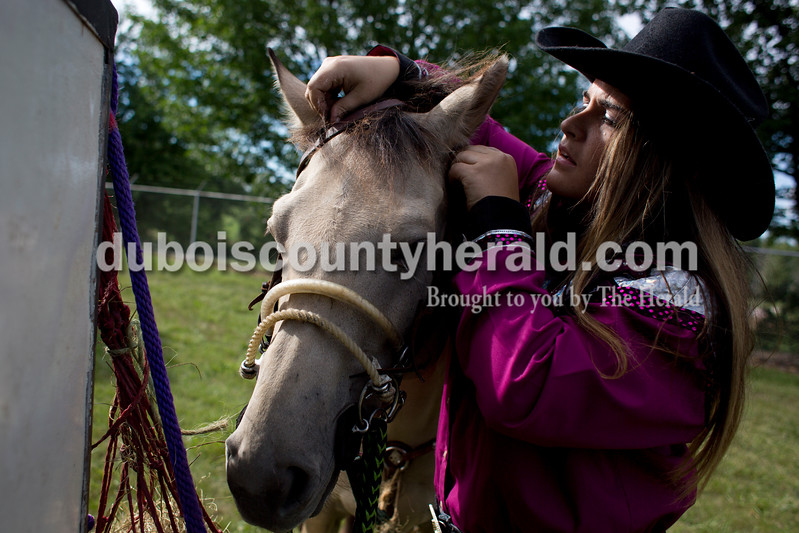 """Tegan Johnston/The Herald<br /> Candace Clark of Shoals put the bridle on her horse """"Hollywood"""" before competing in the Lone Star Rodeo on Saturday at the Dubois County 4-H Fairgrounds in Bretzville."""
