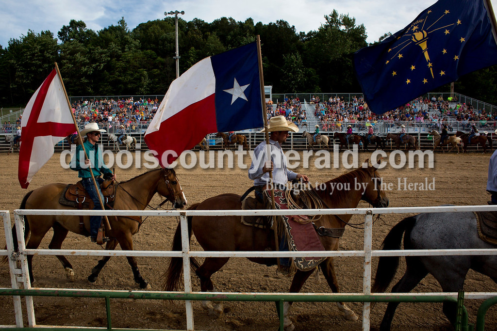 Tegan Johnston/The Herald<br /> Participants parade around the arena during the opening ceremony of the Lone Star Rodeo on Saturday at the Dubois County 4-H Fairgrounds in Bretzville.