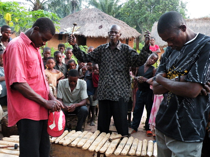 'Mozart' Mukenge (center) prayed a 'Prayer of a Musician' before giving a village concert in the Democratic Republic of the Congo.<br /> <br /> Prayer of a Musician:<br /> <br /> Jehovah God, You created the heavens and earth,<br /> You created everything in the world,<br /> You created the highest mountains,<br /> And you created the great oceans.<br /> Before you there is no other.<br /> You are God of the whole earth<br /> You are father of our King, Jesus Christ<br /> And our father as well.<br /> All glory and honor to you<br /> Because you have kept us safe.<br /> Begin and end with us.<br /> May fighting, quarrels, and worldly thoughts descend<br /> with the waters.<br /> May all this be done in the name of Jesus.<br /> Amen.