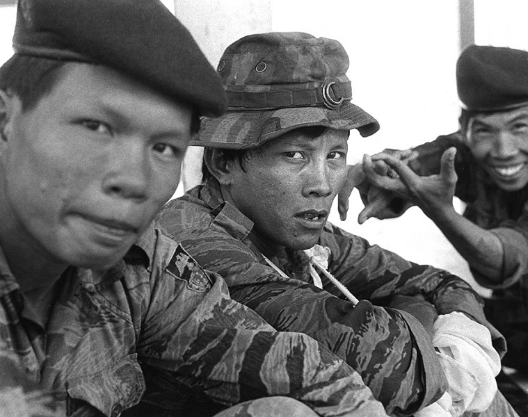 "A Vietnamese soldier gets wounded. His eyes say he's in pain and has little time for my camera and guys like me. The Seal Team patch on his arm says he does different work. Sailors who ""get over"" taking pictures all day are not his cup of tea. ""To hell with you,"" he accuses with his stare. But the guy in the back has something strange to say. He laughs and gestures to the village I had just briefly visited. He thinks he knows what I was looking for. I fly with the wounded to the hospital ship. I take pictures all day."