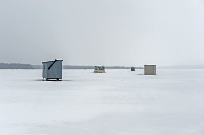 Ice fishing huts on frozen lake