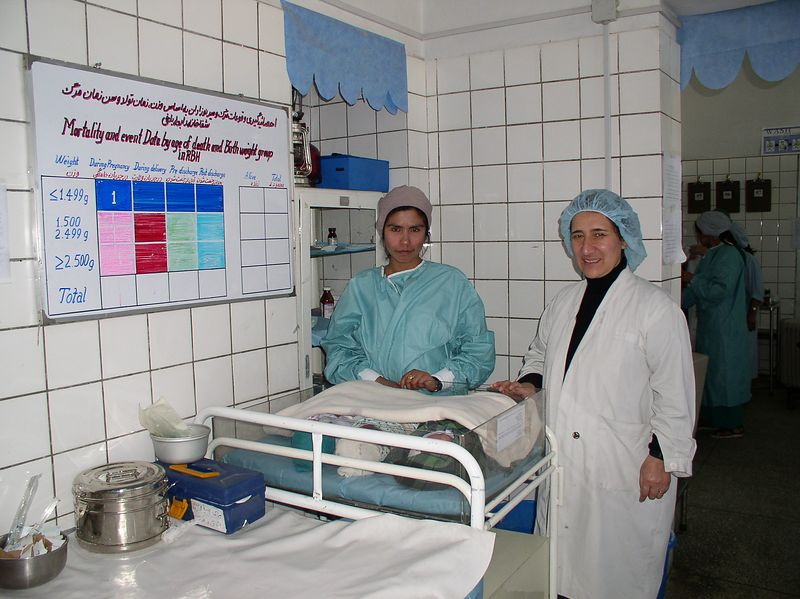 """Pashtoon Azfar, (right) - my """"sister girlfriend"""" in Afghanistan. She is extraordinary and has worked diligently over the past 5 months. Here she is posing with 3 babies (in the bed) and a nurse midwife. On the wall is the """"BABIES"""" matrix, thanks to Pashtoon EVERY newborn is weighed and every WEIGHT counts in program planning."""