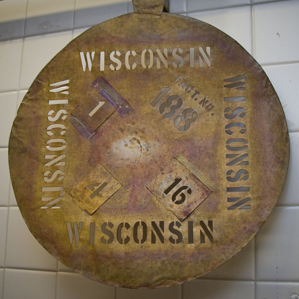 Master cheesemaker Bruce Workman uses a vintage Wisconsin cheese<br /> stencil on his wheels of Emmenthaler.